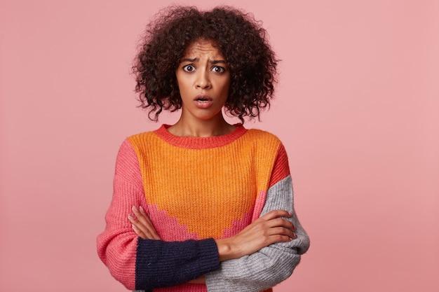 Jovem menina linda morena com cabelo afro parece chocada, estupefata, queixo caído, encara, em pé com os braços cruzados. retrato de mulher que se sente confusa, ofendida, isolada sobre uma parede rosa