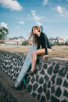 Jovem menina linda posando na praia com uma prancha de surf, mulher surfista, ondas do mar