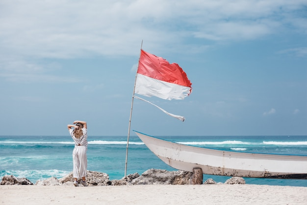 Jovem menina linda posando na praia, oceano, ondas, sol brilhante e pele bronzeada