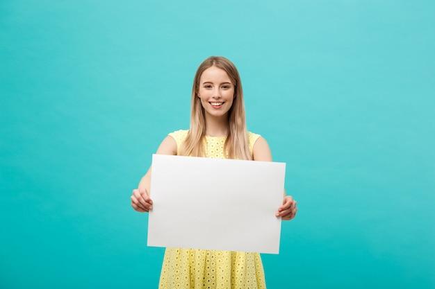 Jovem menina linda sorrindo e segurando uma folha de papel em branco, vestida de amarelo