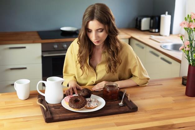 Jovem menina linda tomando café da manhã em casa na cozinha. a garota come alimentos não saudáveis e de alta caloria.