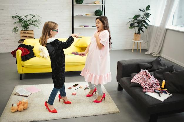 Jovem menina loira apontando nela frined. eles ficam no quarto e usam roupas para mulheres adultas. morena parece animada. eles posando.