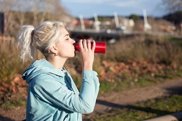 Jovem menina loira bebendo água durante a corrida de manhã