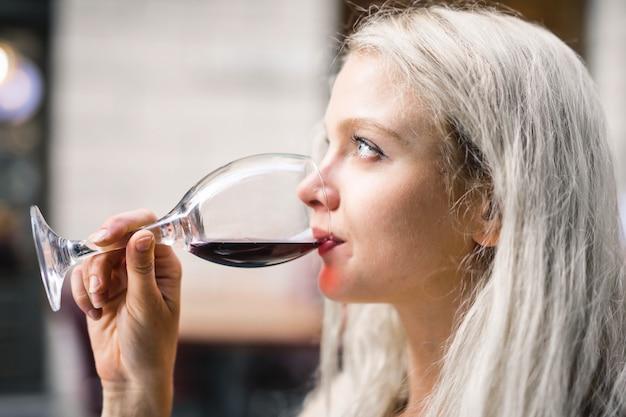 Jovem menina loira bebendo vinho