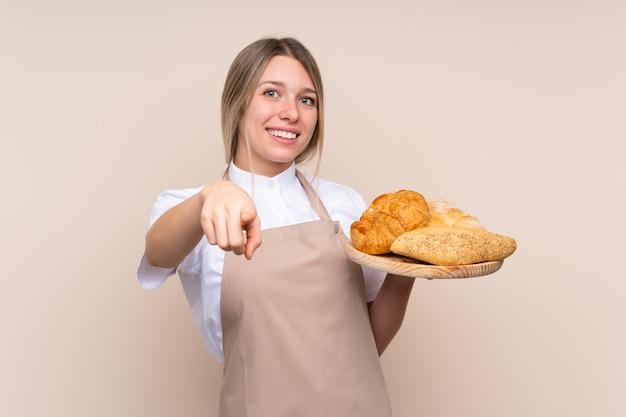 Jovem menina loira com avental. padeiro feminino segurando uma mesa com vários pães aponta o dedo para você com uma expressão confiante