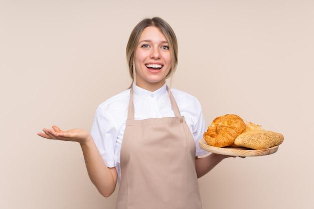 Jovem menina loira com avental. padeiro feminino segurando uma mesa com vários pães com expressão facial chocado