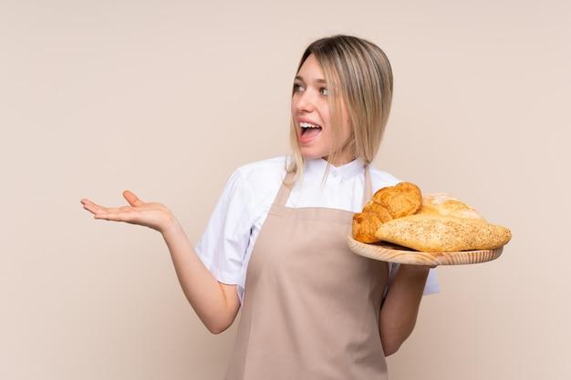 Jovem menina loira com avental. padeiro feminino segurando uma mesa com vários pães com expressão facial de surpresa
