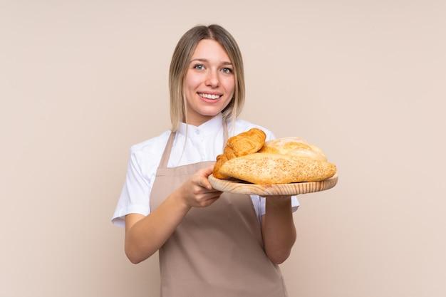 Jovem menina loira com avental. padeiro feminino segurando uma mesa com vários pães com expressão feliz