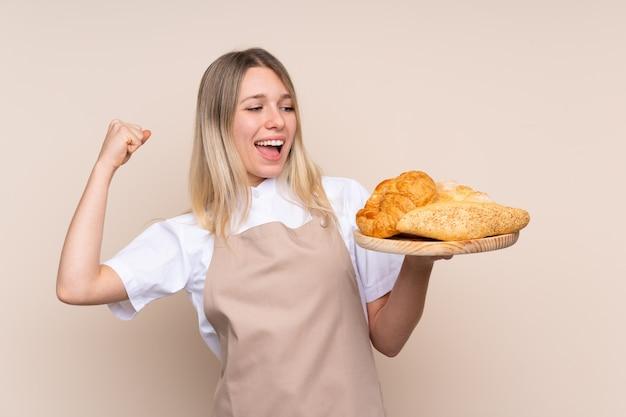 Jovem menina loira com avental. padeiro feminino segurando uma mesa com vários pães comemorando uma vitória