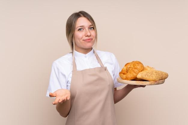 Jovem menina loira com avental. padeiro feminino segurando uma mesa com vários pães, fazendo dúvidas gesto enquanto levanta os ombros