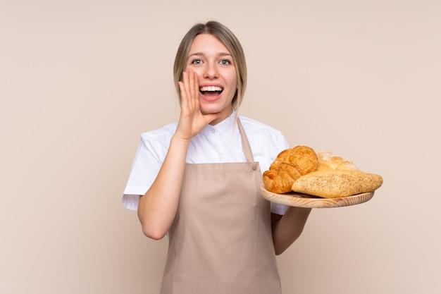 Jovem menina loira com avental. padeiro feminino segurando uma mesa com vários pães gritando com a boca aberta