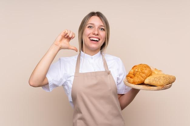 Jovem menina loira com avental. padeiro feminino segurando uma mesa com vários pães, orgulhosos e satisfeitos