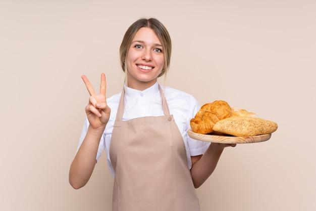 Jovem menina loira com avental. padeiro feminino segurando uma mesa com vários pães, sorrindo e mostrando sinal de vitória