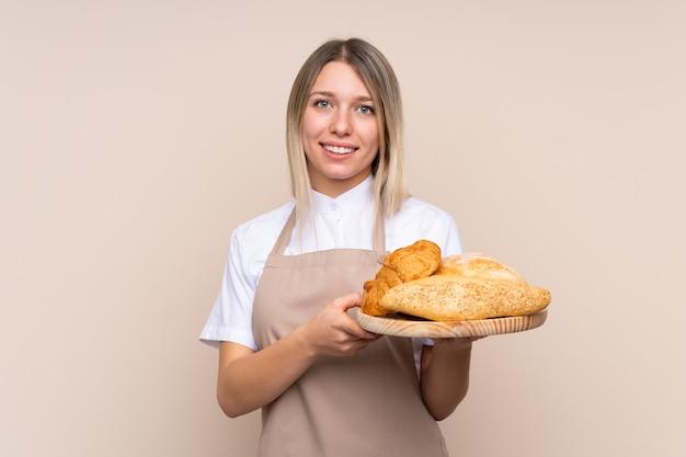 Jovem menina loira com avental. padeiro feminino segurando uma mesa com vários pães, sorrindo muito