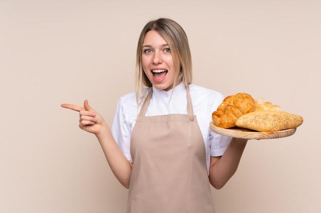 Jovem menina loira com avental. padeiro feminino segurando uma mesa com vários pães surpreso e apontando o dedo para o lado