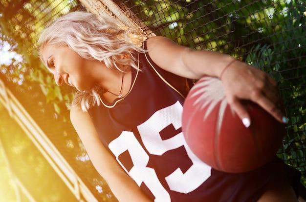 Jovem menina loira com basquete laranja posando ao ar livre