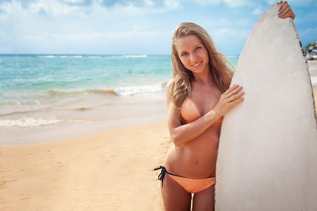 Jovem menina loira com corpo perfeito em biquíni segurando o cartaz de aula de surf e sorrindo