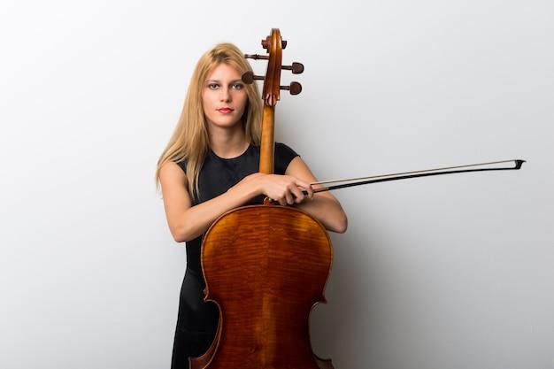 Jovem menina loira com seu violoncelo posando na parede branca