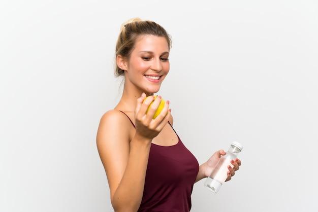 Jovem menina loira com uma maçã e uma garrafa de água