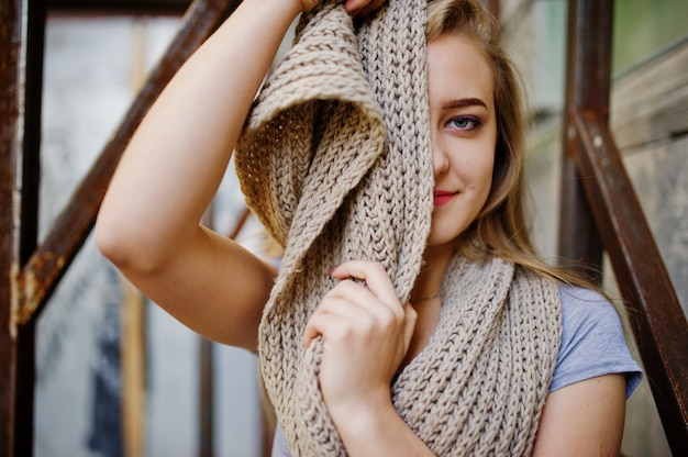 Jovem menina loira de saia preta com lenço colocado na rua da cidade, perto da armadura de ferro.