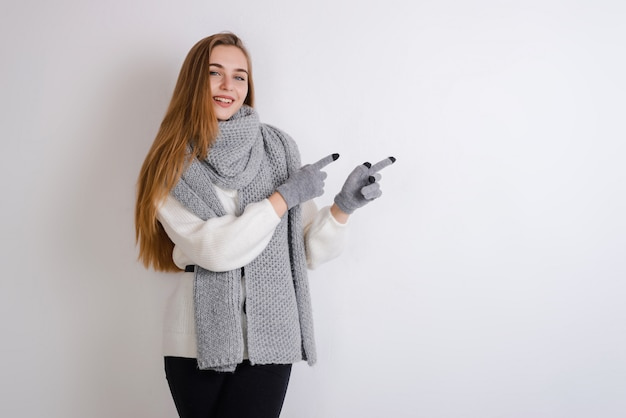 Jovem, menina loira em luvas e cachecol mostra na parede vazia, copie o espaço