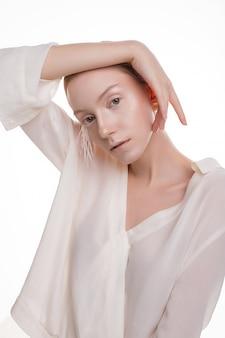 Jovem menina loira em roupa branca posando