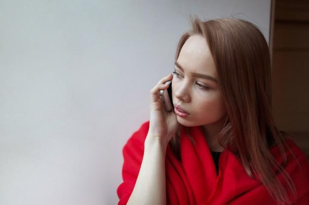 Jovem menina loira falando ao telefone.