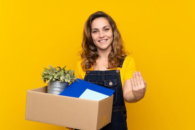 Jovem menina loira fazendo um movimento ao pegar uma caixa cheia de coisas convidando para vir com a mão. feliz que você veio