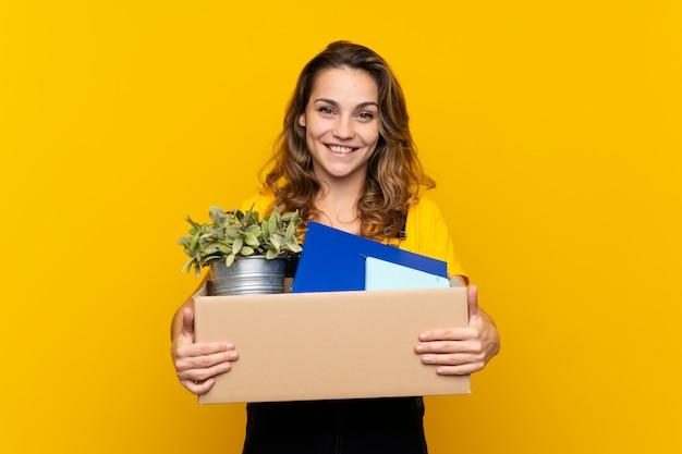 Jovem menina loira fazendo um movimento ao pegar uma caixa cheia de coisas