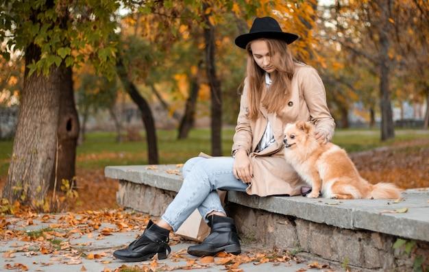 Jovem menina loira natural com um chapéu preto senta-se em um parque de outono