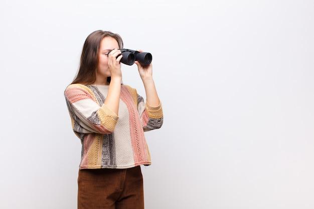 Jovem menina loira segurando um binóculo contra parede branca