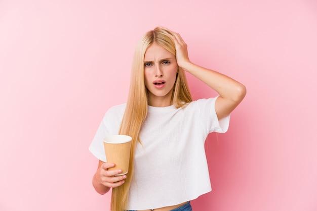 Jovem menina loira segurando um café para viagem sendo chocado, ela se lembrou de uma reunião importante.