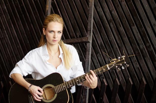 Jovem menina loira sexy tocando violão