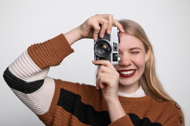 Jovem menina loira sorrindo, segurando a câmera fotográfica vintage, tirando foto