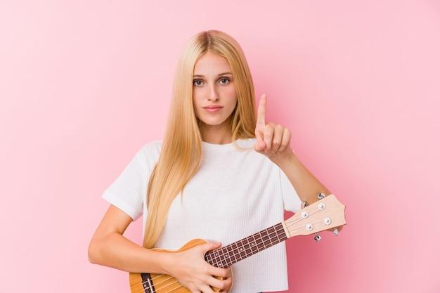 Jovem menina loira tocando ukelele mostrando o número um com o dedo.
