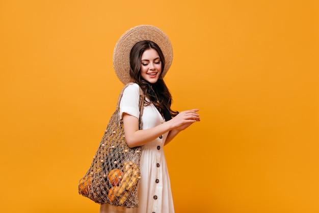 Jovem menina morena carrega sacola de compras com frutas. senhora de chapéu e vestido branco olha para baixo em fundo laranja.