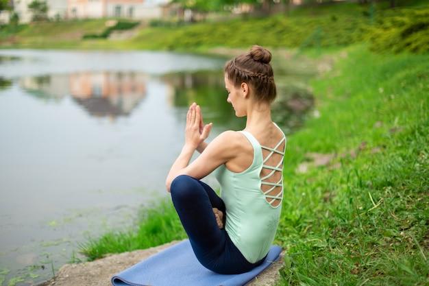 Jovem menina morena caucasiana bonita fazendo yoga em um gramado verde contra o rio