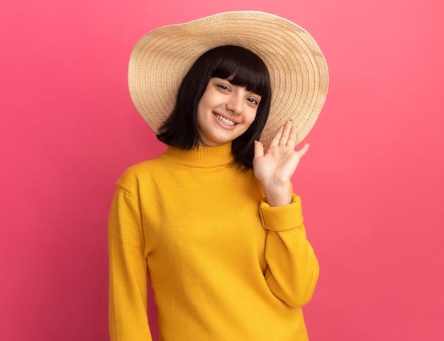 Jovem menina morena caucasiana sorridente com chapéu de praia fica com a mão levantada isolada na parede rosa com espaço de cópia