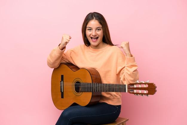 Jovem menina morena com guitarra isolado rosa comemorando uma vitória