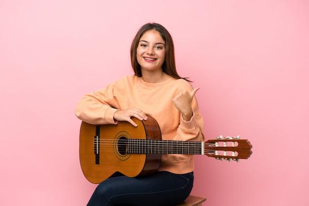 Jovem menina morena com guitarra sobre parede rosa isolada com polegares para cima, porque algo de bom aconteceu