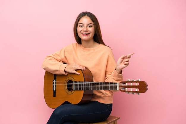 Jovem menina morena com guitarra sobre rosa isolado surpreendeu e apontando o dedo para o lado