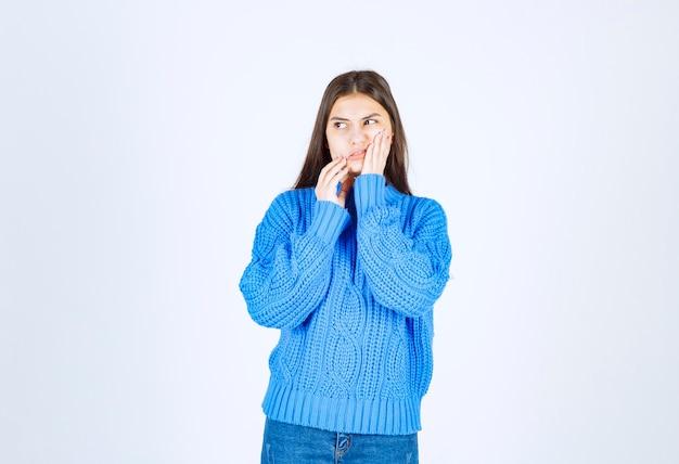 Jovem menina morena com suéter azul tendo dor de dente em branco.
