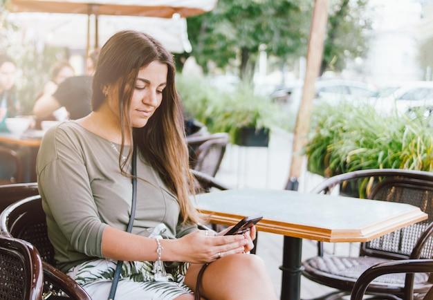 Jovem menina morena de cabelos longos sorridente vestido casual usando móveis no café de rua