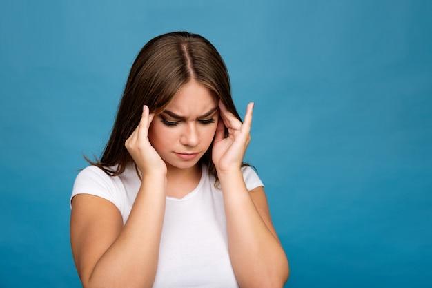 Jovem menina morena de camiseta branca, sofrendo de dor de cabeça, fundo azul