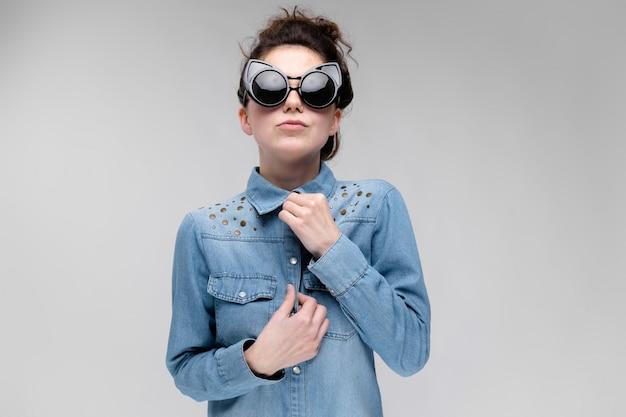 Jovem menina morena de óculos escuros. óculos de gato. o cabelo está reunido em um coque. a garota ajusta a blusa.