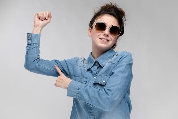 Jovem menina morena de óculos escuros óculos de gato o cabelo está reunido em um coque a menina aponta o dedo para o músculo