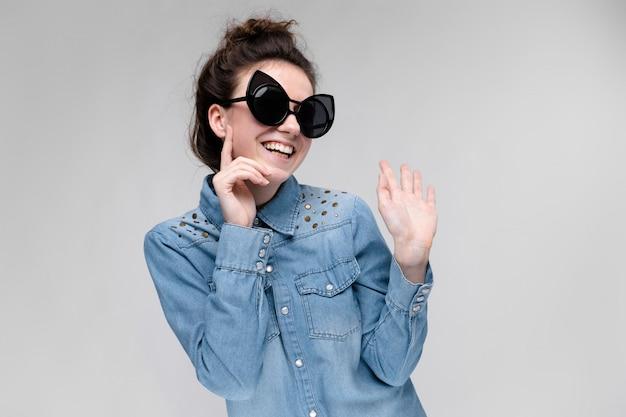Jovem menina morena de óculos escuros óculos de gato o cabelo está reunido em um coque a menina colocou um dedo na bochecha a menina está rindo