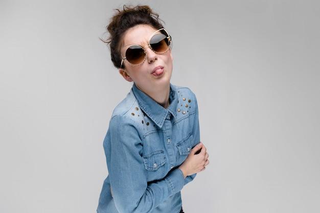 Jovem menina morena de óculos escuros óculos de gato o cabelo está reunido em um coque a menina mostra a língua