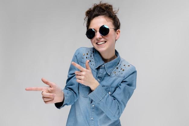 Jovem menina morena de óculos redondos. os cabelos são reunidos em um coque. a garota aponta com os dedos.