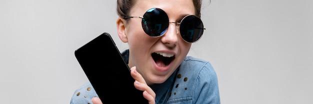 Jovem menina morena de óculos redondos. os cabelos são reunidos em um coque. menina com um telefone preto.
